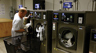 Man pulling out towels from a Sports laundry Systems Washer-extractor