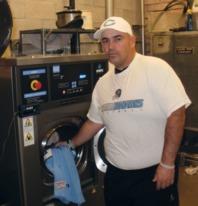 Cabrillo College equipment room manager standing next to a Sports Laundry System Washer-extractor