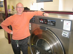 laundry owner with washing machine in laundromat